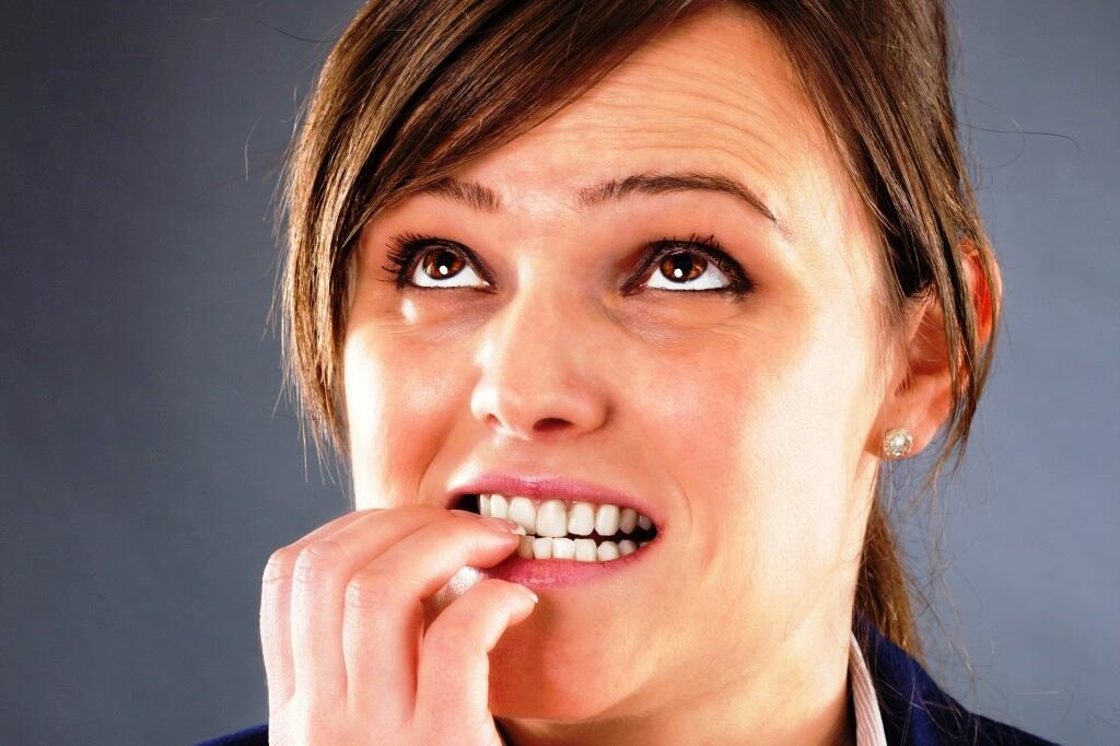 Closeup portrait of a nervous young businesswoman biting her fingers