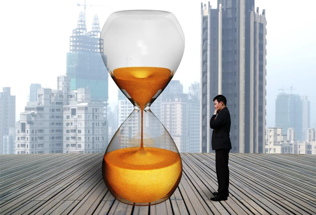standing businessman thinking with hourglass