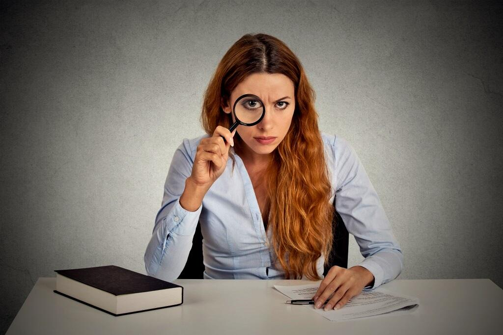 woman with glasses skeptically looking at you through magnifying glass