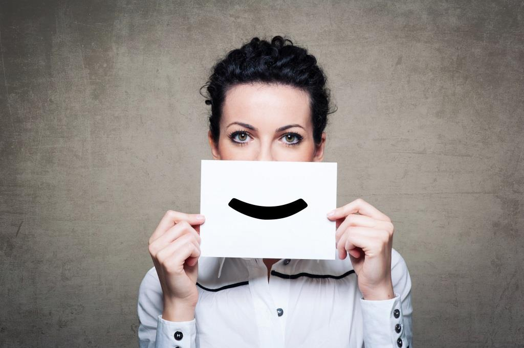 Young businesswoman hiding his face with a white billboard with a smiley face on it.