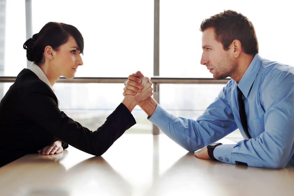Businessman and businesswoman arm wrestling