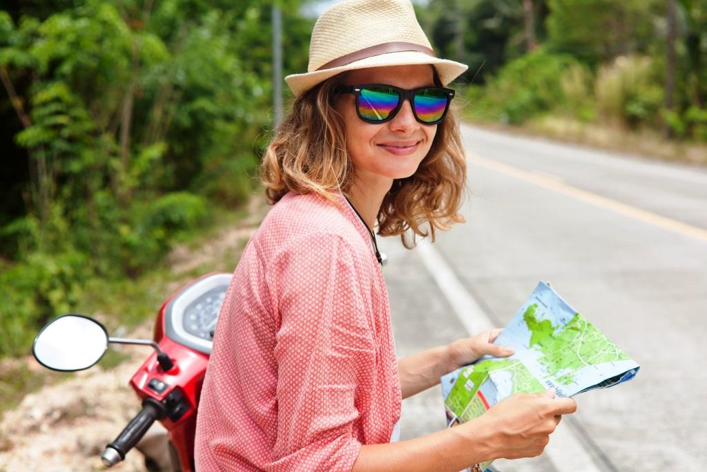 Beautiful young woman with map in hand and a motorbike on the road. Travel, navigation, tourism