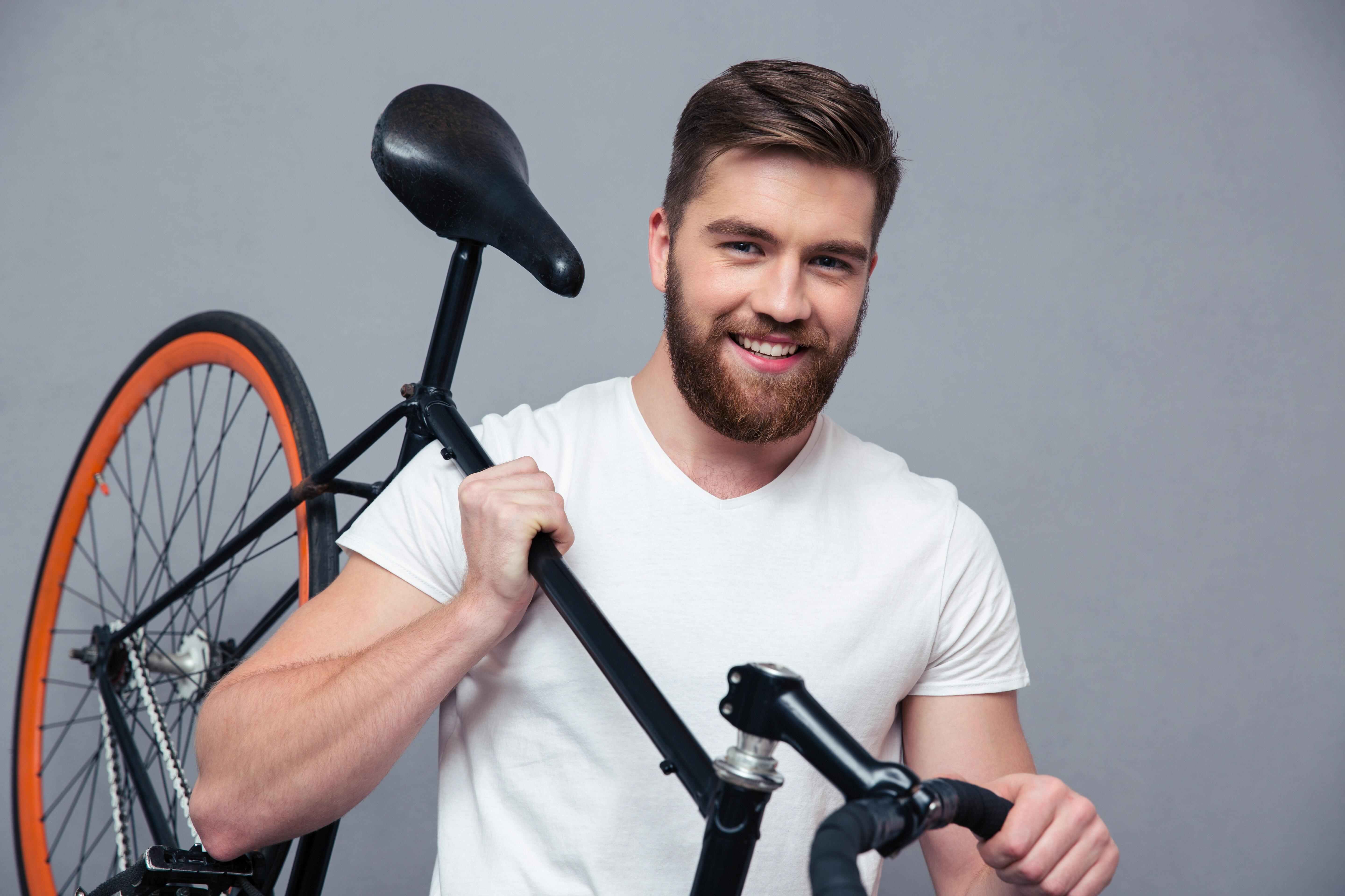 Smiling casual man holding bicycle on the shouder